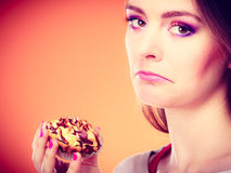 Unhappy woman holds cake in hand Royalty Free Stock Images