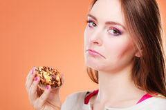 Unhappy woman holds cake in hand. Diet dilemma, grow fat from eating sweets concept. Sad unhappy woman holds cake cupcake in hand orange background Stock Images