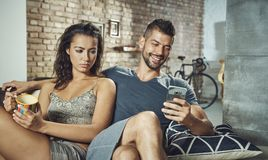 Unhappy woman looking at boyfriend jealous. Unhappy women looking at boyfriend jealous as reading text message on mobilephone Royalty Free Stock Image