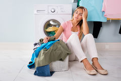 Unhappy Woman Looking At Clothes In Utility Room. Young Unhappy Woman Looking At Pile Of Dirty Clothes Near Washing Machine At Utility Room royalty free stock images