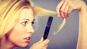 Unhappy woman looking through magnifier destroyed hair Royalty Free Stock Images