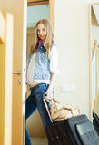 Unhappy woman with luggage leaving  home Royalty Free Stock Images