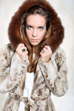 Unhappy woman in luxurious fur coat. Beautiful long-haired model posing in a fur coat with unhappy expression Stock Photos
