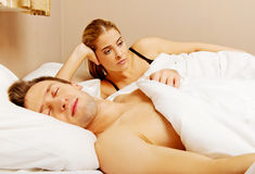 Unhappy woman lying in bed stressed when her husband sleeping Royalty Free Stock Photography