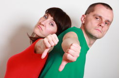 Unhappy woman and man showing thumbs down Stock Photos