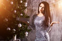 Unhappy woman near Christmas tree, don`t like the gift royalty free stock photo