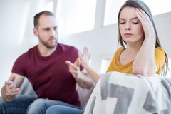 Unhappy woman not wanting to talk with her man. Leave me alone. Nice upset broken-hearted young women feeling awful and not wanting to be alone and he men trying Stock Images