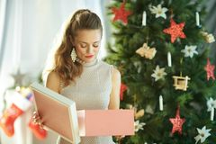 Unhappy woman with opened Christmas gift near Christmas tree. Unhappy young woman with opened Christmas present box near Christmas tree royalty free stock photo