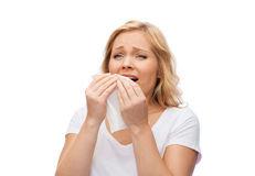 Unhappy woman with paper napkin sneezing. People, healthcare, rhinitis, cold and allergy concept - unhappy woman with paper napkin sneezing Royalty Free Stock Photo