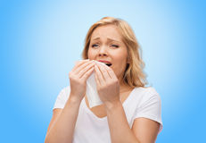 Unhappy woman with paper napkin sneezing Royalty Free Stock Photography