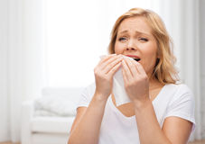 Unhappy woman with paper napkin sneezing Stock Images