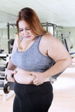 Unhappy woman pinching her belly fat. Blonde woman standing in the fitness center while pinching her belly fat and looks unhappy Royalty Free Stock Photos