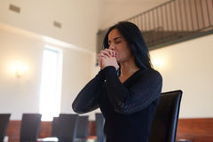 Unhappy woman praying god at funeral in church Royalty Free Stock Photos