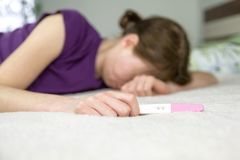 Unhappy woman with pregnant test. Unhappy woman lying on a bed with positive pregnant test royalty free stock image
