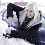 Unhappy woman scraping ice. Off car royalty free stock image