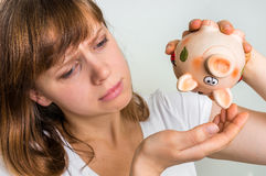 Unhappy woman shaking an empty piggy bank Royalty Free Stock Photography