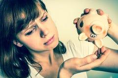 Unhappy woman shaking an empty piggy bank - retro style Stock Photos