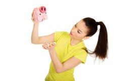 Unhappy woman shaking piggybank. Stock Photos
