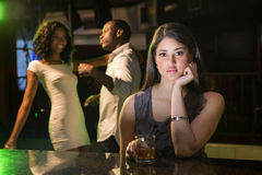 Unhappy woman sitting at bar counter and couple dancing behind her Royalty Free Stock Photos