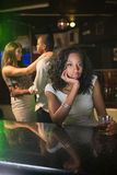 Unhappy woman sitting at bar counter and couple dancing behind her Stock Photos