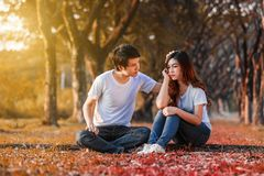 Unhappy woman sitting with a concerned guy comforting her in par royalty free stock photography