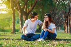 Unhappy woman sitting with a concerned guy comforting her in par. Unhappy women sitting with a concerned guy comforting her in the park Royalty Free Stock Photography