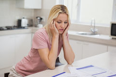 Unhappy woman with sitting in kitchen Royalty Free Stock Photography