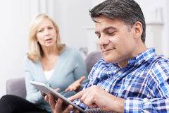 Unhappy Woman Sitting On Sofa As Partner Uses Digital Tablet Royalty Free Stock Images