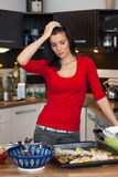 Unhappy woman standing in kitchen Stock Photo