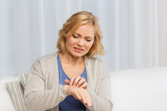 Unhappy woman suffering from hand inch at home Stock Image