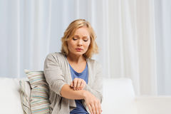 Unhappy woman suffering from hand inch at home royalty free stock photos