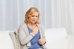 Unhappy woman suffering from heartache at home. People, healthcare, heart disease and problem concept - unhappy woman suffering from heartache at home Stock Image