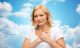 Unhappy woman suffering from heartache. People, healthcare, heart disease and problem concept - unhappy woman suffering from heartache over blue sky and clouds Royalty Free Stock Photo