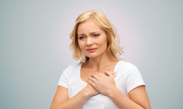 Unhappy woman suffering from heartache. People, healthcare, heart disease and problem concept - unhappy woman suffering from heartache over gray background Stock Photo