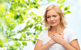 Unhappy woman suffering from heartache. People, healthcare, heart disease and problem concept - unhappy woman suffering from heartache over green natural Stock Photos