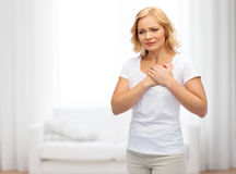Unhappy woman suffering from heartache. People, healthcare, heart disease and problem concept - unhappy woman suffering from heartache over living room Stock Photo