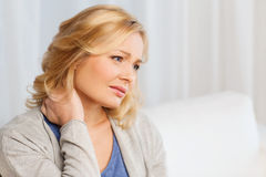 Unhappy woman suffering from neck pain at home Stock Image