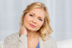 Unhappy woman suffering from neck pain at home Stock Photos