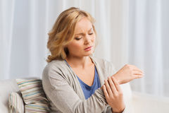 Unhappy woman suffering from pain in hand at home Royalty Free Stock Images