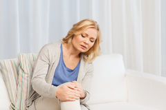 Unhappy woman suffering from pain in leg at home Stock Photo
