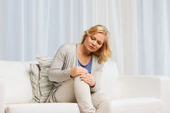 Unhappy woman suffering from pain in leg at home Royalty Free Stock Photography