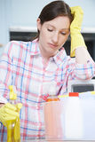 Unhappy Woman Surrounded By Cleaning Products At Home Stock Photo