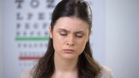 Unhappy woman taking glasses off, suffering high pressure, risk of losing sight. Stock footage stock video footage