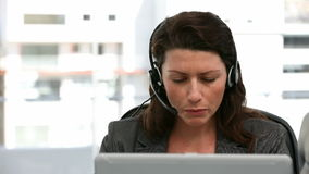 Unhappy woman talking on the headphone stock footage