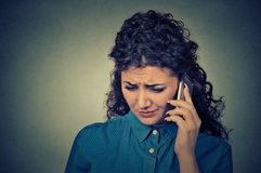 Unhappy woman talking on mobile phone looking down. Human face expression Stock Images