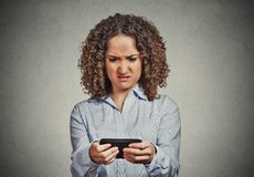 Unhappy woman texting on phone with disgusted face Stock Image