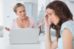 Unhappy woman thinking while her friend is getting angry at her Stock Photos