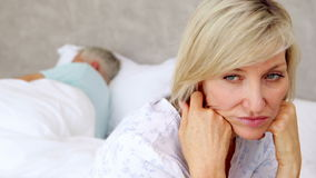 Unhappy woman thinking while her husband is sleeping. At home in bedroom stock video