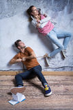 Unhappy woman with tied ankle. Content men and unhappy women with rope tied around ankle Stock Photos