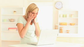 Unhappy woman using her laptop. In her kitchen stock video